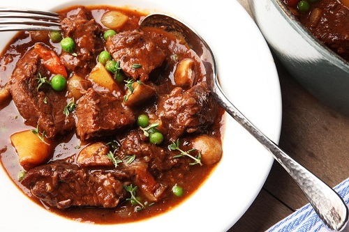 An American Beef Stew on Plate with a spoon in it