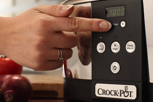 Touching Crockpot Next Generation Cooker Digital Screen with Hand