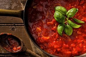 A red pasta sauce cooking with fresh basil on top