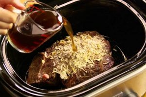 Someone Pouring Red wine over a roast in a Slow Cooker