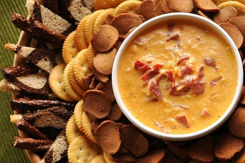 A Slow Cooker Reuben Dip on a platter with chips and crackers
