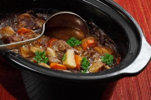 An Irish Stew in Slow Cooker being scooped up