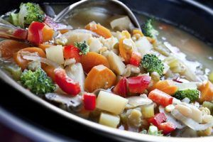 A Slow Cooker veggie Stew being scooped up