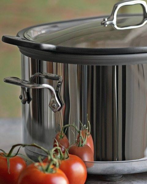 A Metal pressure cooker with tomatoes on the side