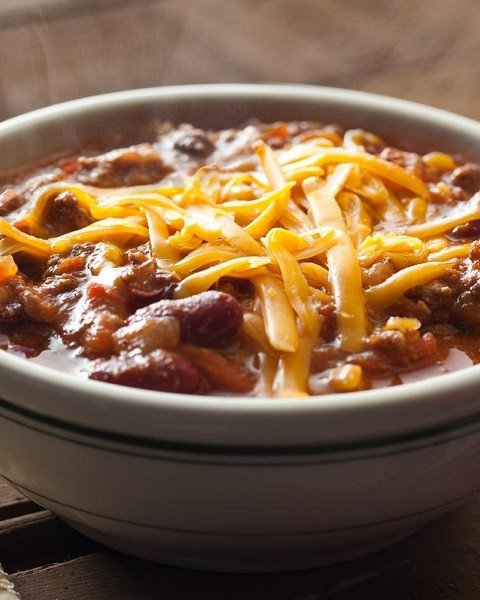 A bowl of chili with cheese melting on the top