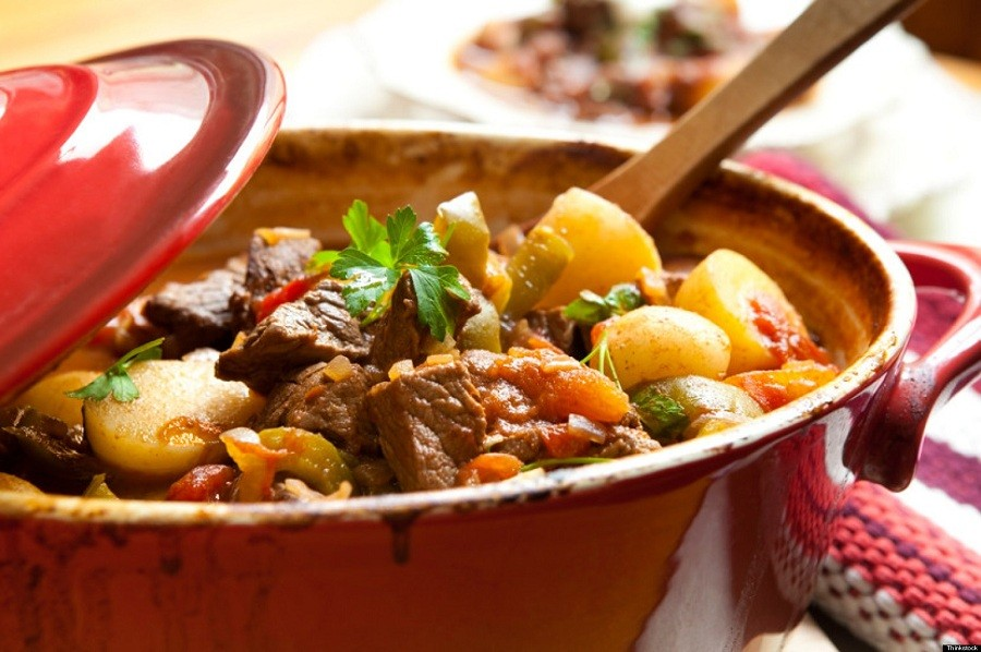 A red bowl of meat and potatoes and veggies made in a pressure cooker