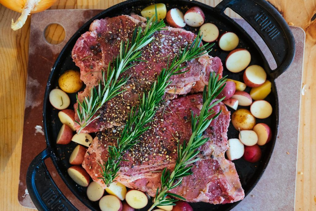 cast iron with meat, potatoes, and rosemary uncooked